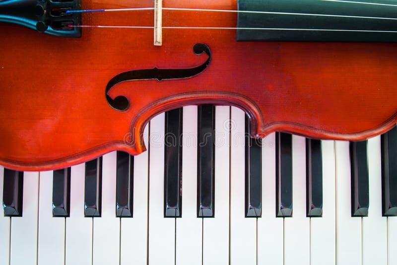Fiol på piano royaltyfri bild