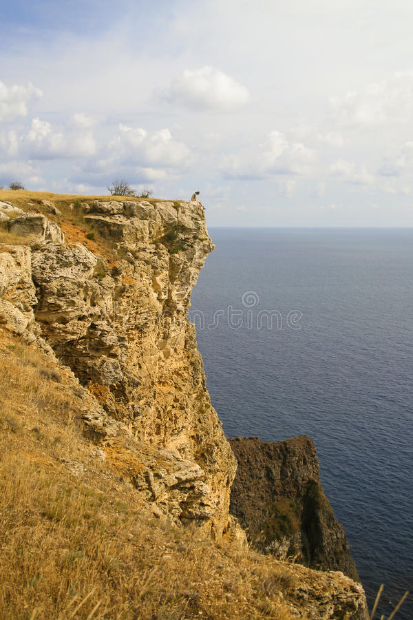 Fiolent cape. Lonely Man sitting on edge of the cliff in Fiolent cape, Crimea stock image