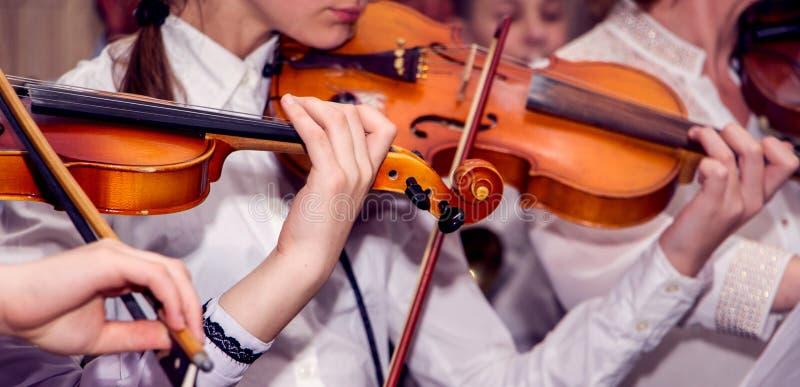 Fioler för barnlek under konserten Utföra klassisk musik på Violins_ royaltyfria bilder