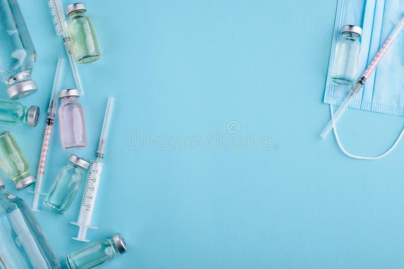 Fioles, seringues et masque photo stock