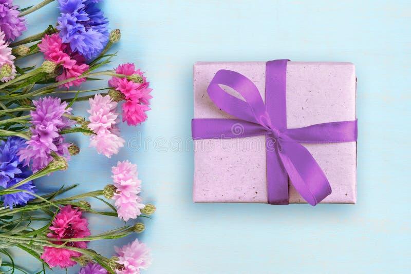Fiordalisi e contenitore di regalo sul blu immagine stock