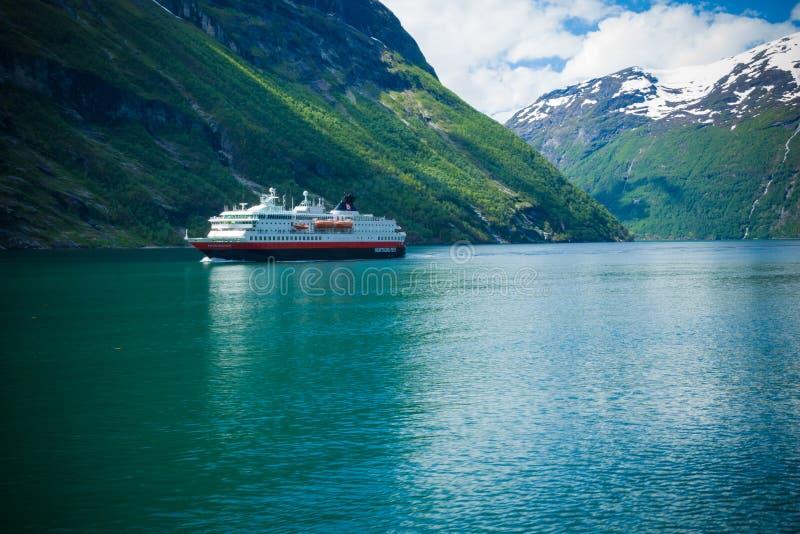 Fiordo de Geiranger, Noruega-JUNIO 15,2012: el transbordador Hurtigruten de la traves?a navega a lo largo de Geirangerfjord El vi imagen de archivo libre de regalías
