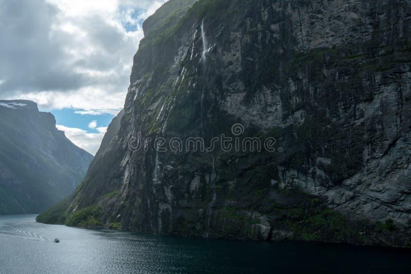 Fiordo masivo del geiranger en Noruega vista de un barco de cruceros con el brillo ligero a través de las nubes y de la cascada imágenes de archivo libres de regalías