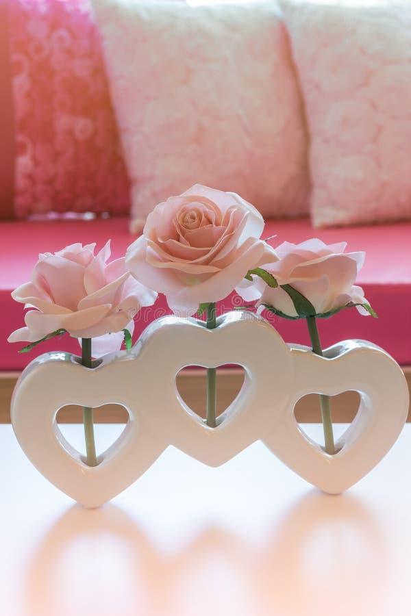 Fiore artificiale della rosa di rosa in vaso di forma del cuore fotografia stock
