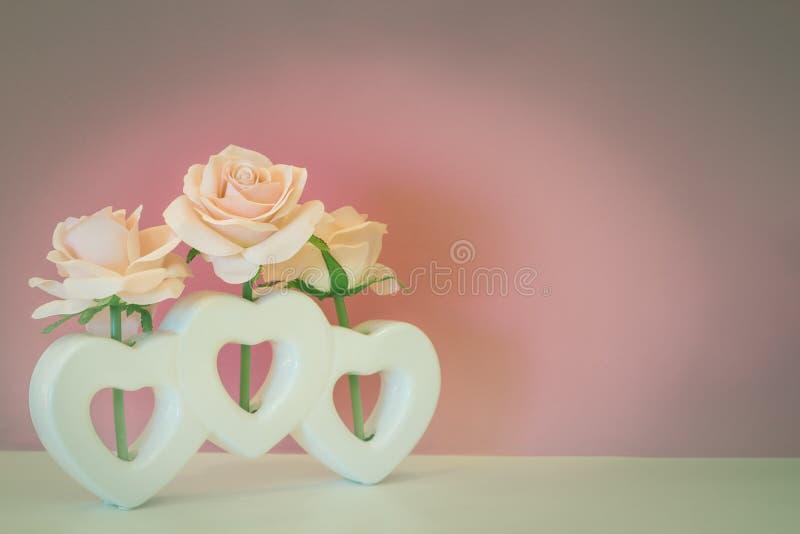 Fiore artificiale della rosa di rosa in vaso di forma del cuore immagini stock