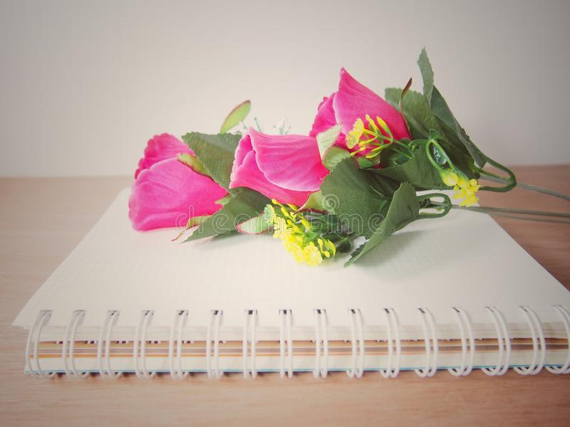 Fiore artificiale rosa delle rose del mazzo sul libro con la spirale immagini stock libere da diritti