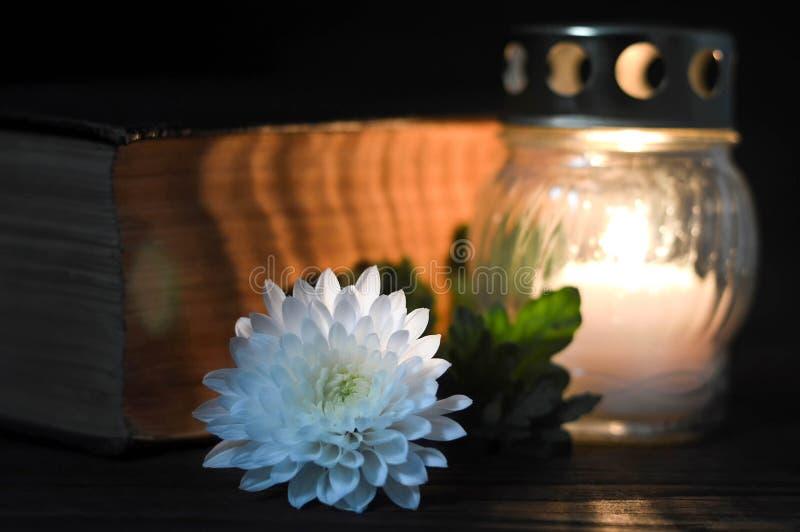 Fiore bianco del crisantemo, candela commemorativa e libro fotografia stock libera da diritti