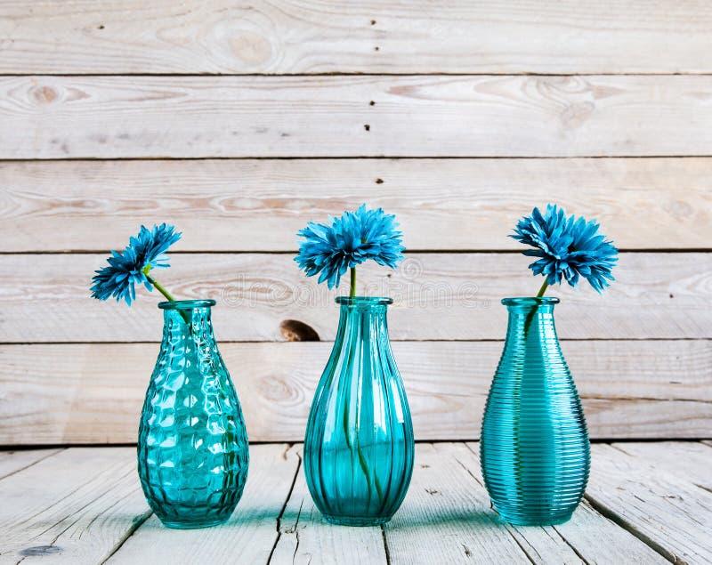 Fiore blu della gerbera in un vaso su fondo di legno fotografia stock