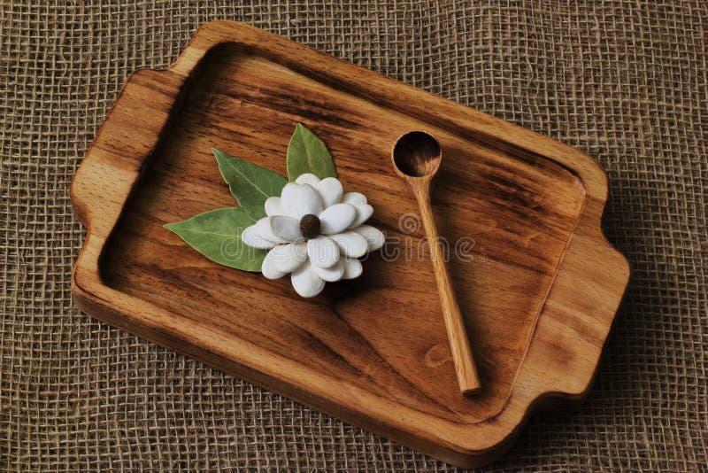 Fiore casalingo originale dai semi di zucca e dalle foglie della baia con il cucchiaio di legno sul vassoio del faggio su fondo h fotografia stock libera da diritti