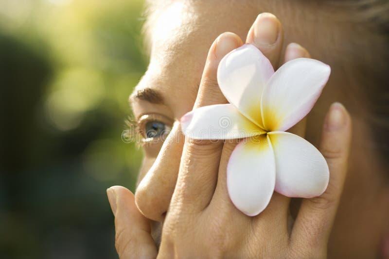 Fiore della holding della donna sopra l'occhio immagini stock