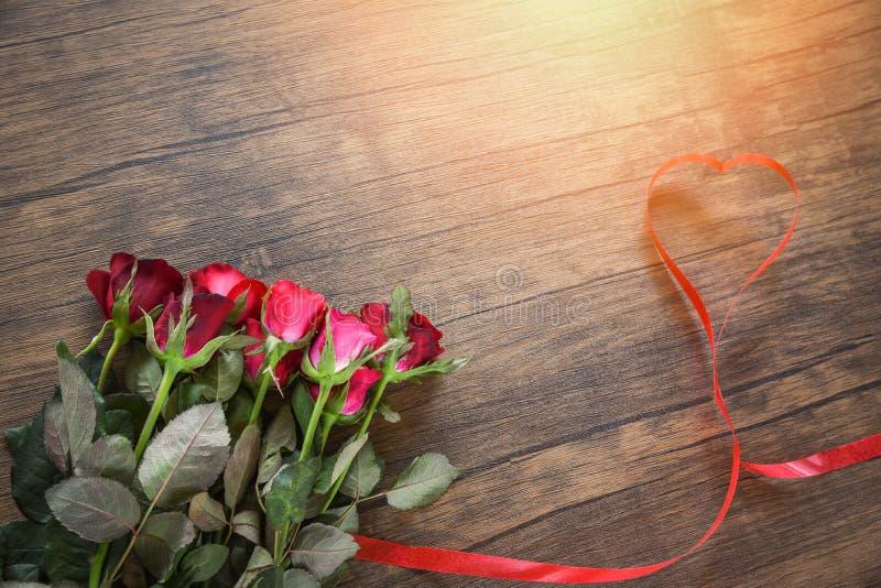 Fiore della rosa rossa di giorno di biglietti di S. Valentino su fondo di legno/su cuore rosso con le rose fotografia stock libera da diritti