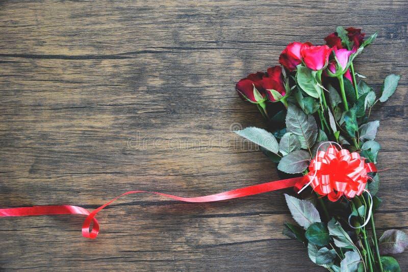 Fiore della rosa rossa di giorno di biglietti di S. Valentino su fondo di legno/su cuore rosso con le rose e sul nastro rosso fotografia stock libera da diritti