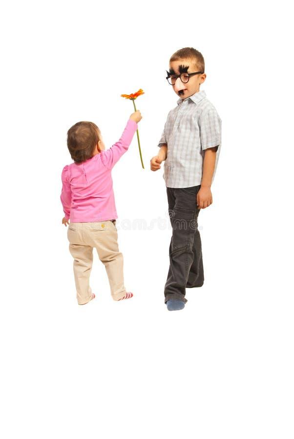 Fiore di offerta della bambina al ragazzo immagini stock