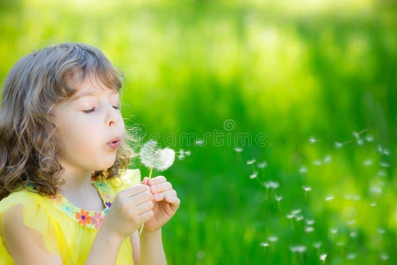 Fiore di salto del dente di leone del bambino felice all'aperto fotografia stock