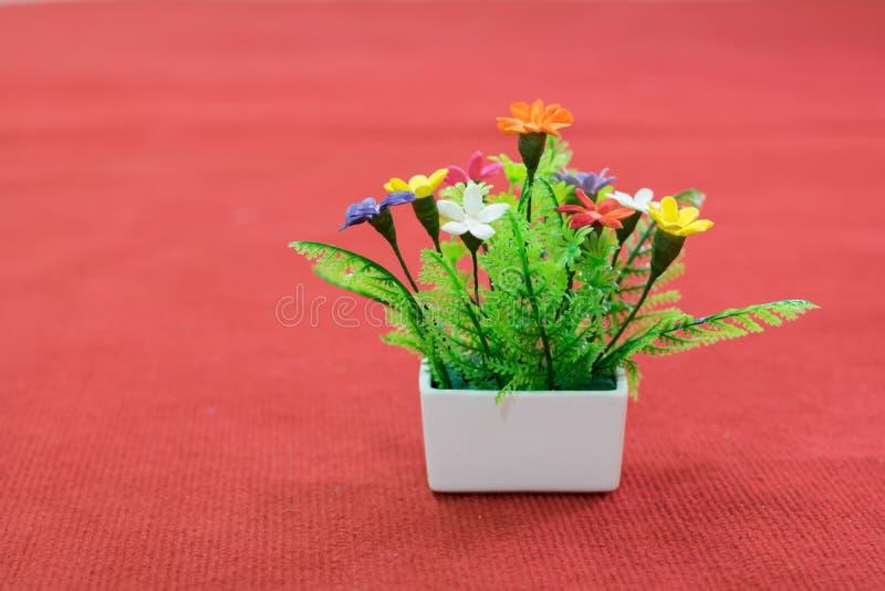 Fiore falso nel vaso da fiori bianco sul pavimento rosso, la falsificazione fotografie stock libere da diritti