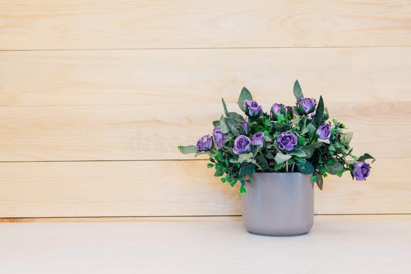 Fiore falso in vaso su fondo di legno fotografia stock libera da diritti