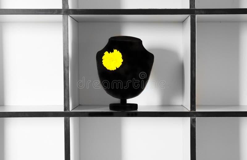 Fiore giallo sull'esposizione nera mick dei gioielli su sulla scatola di modo immagine stock libera da diritti