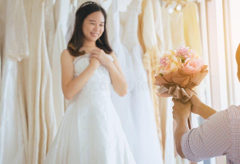Fiore nascondentesi dello sposo dietro la parte posteriore per sorprendere sposa, emozione positiva della donna ed affrontare mom immagini stock