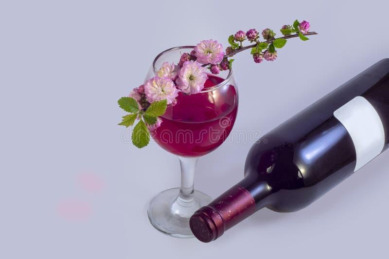 Fiore sakura di Rosa su un vetro di vino rosso accanto ad una bottiglia di vino immagine stock