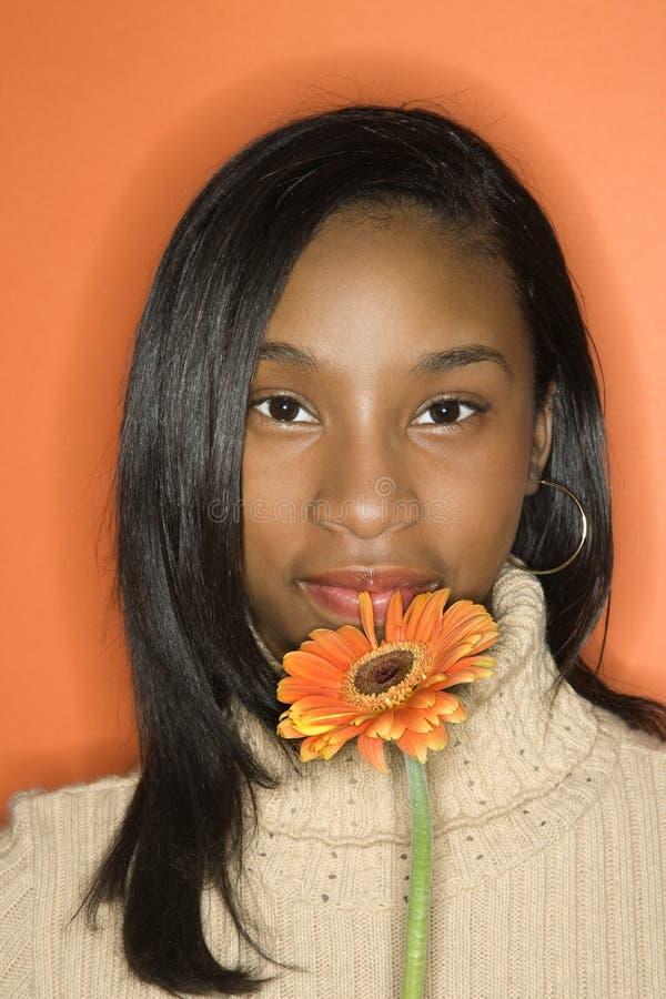 Fiore teenager della holding della ragazza del African-American. immagini stock libere da diritti