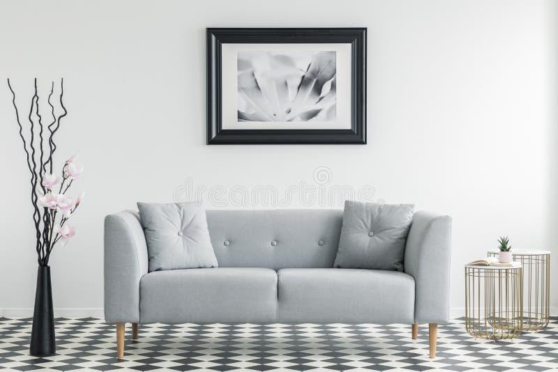 Fiori accanto al sofà grigio con i cuscini in salone minimo i fotografie stock libere da diritti