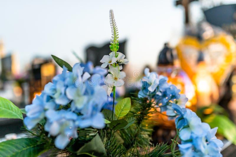 Fiori artificiali e reali e candele accese che si trovano sulla pietra tombale nel cimitero fotografie stock libere da diritti