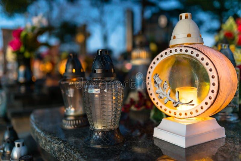 Fiori artificiali e reali e candele accese che si trovano sulla pietra tombale nel cimitero fotografia stock libera da diritti