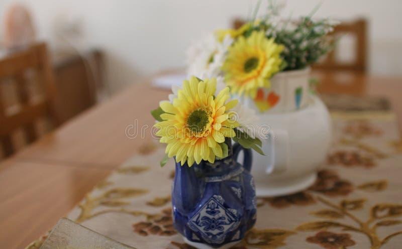 Fiori artificiali in vasi sulla tavola fotografia stock libera da diritti