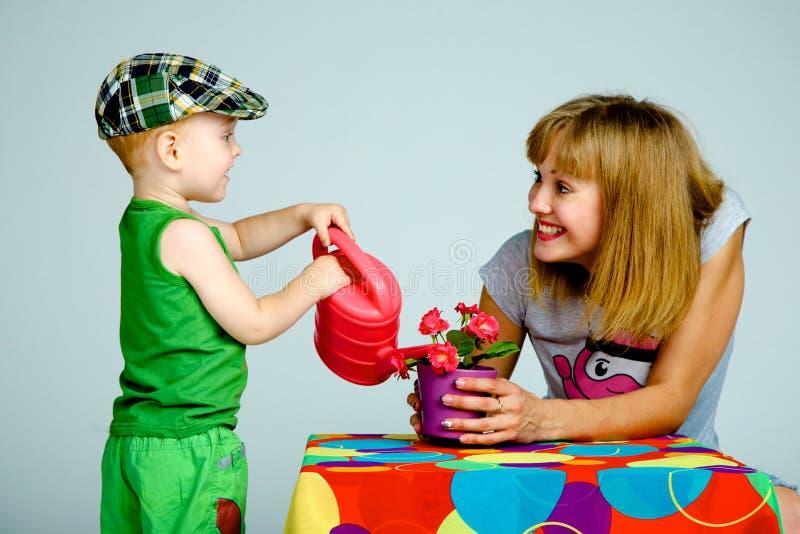 Fiori d'innaffiatura del figlio e della mamma con un annaffiatoio immagine stock libera da diritti