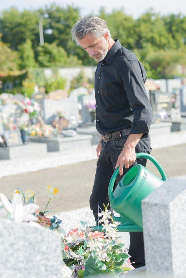 Fiori d'innaffiatura dell'uomo bello maturo al cimitero immagini stock libere da diritti