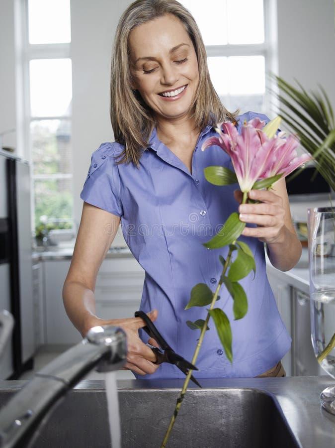 Fiori da taglio sorridenti della donna nel lavandino di cucina immagini stock