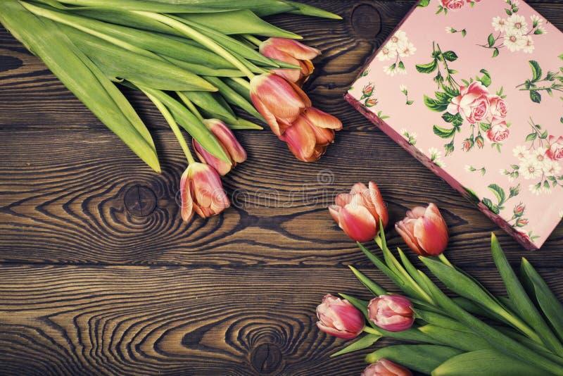 Fiori del contenitore e del tulipano di regalo sulla tavola rustica per il giorno dell'8 marzo, di Giornata internazionale della  immagine stock libera da diritti
