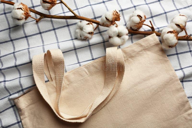Fiori del cotone e borsa lanuginosi di eco su tessuto immagine stock