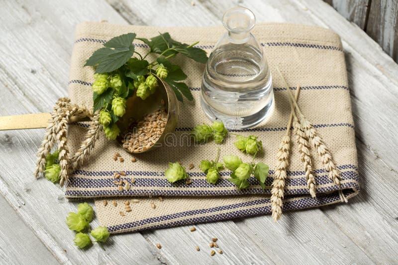 Fiori del luppolo, orecchie del grano e semi, acqua ingredienti per fare birra sulla tavola di legno fotografia stock