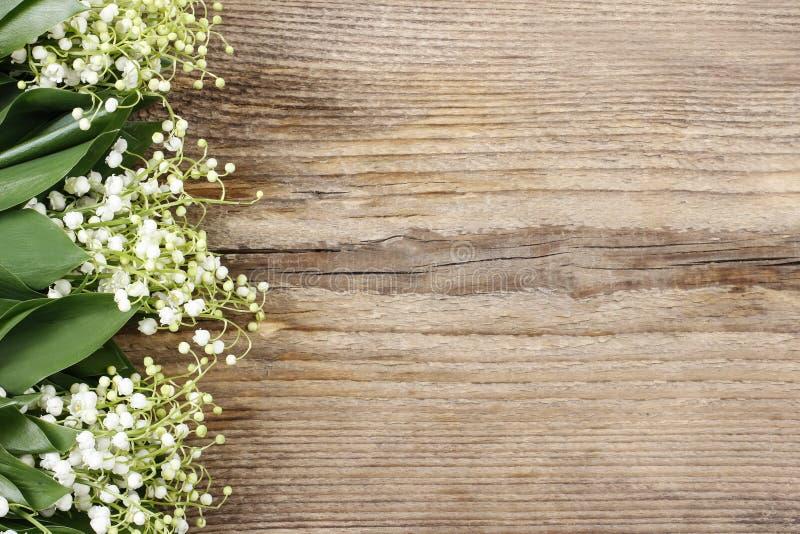 Fiori del mughetto su fondo di legno fotografia stock
