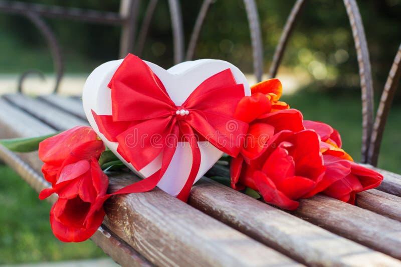 Fiori del tulipano e contenitore di regalo rossi sulla tavola di legno fotografie stock