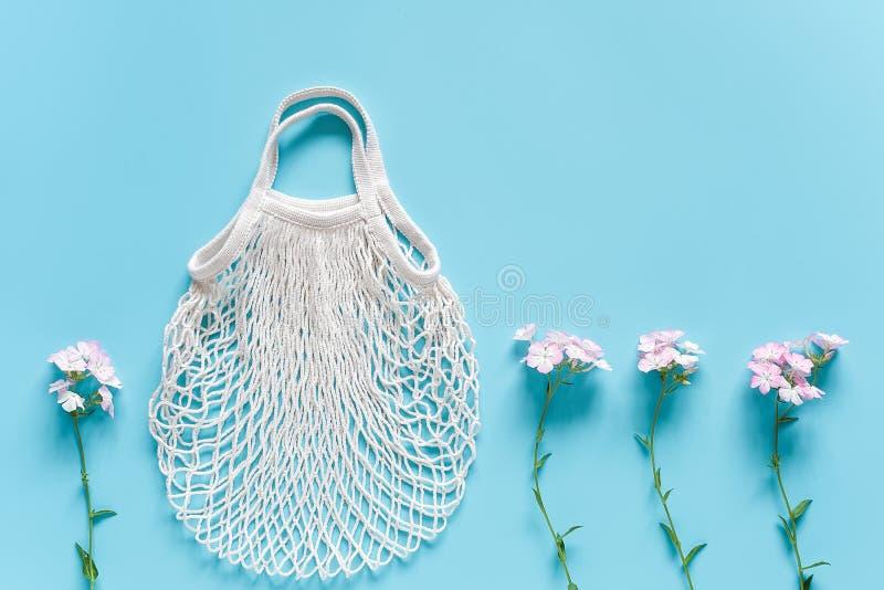 Fiori delicati e borsa di compera riutilizzabile bianca della maglia di eco su fondo blu Concetto nessuno spreco di plastica e ze fotografia stock