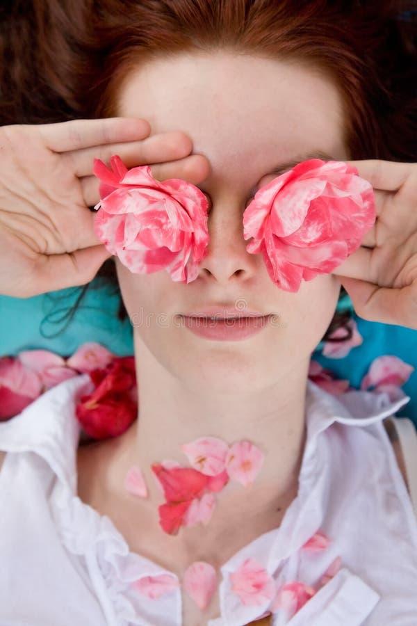 Fiori della holding della giovane donna davanti agli occhi immagine stock libera da diritti