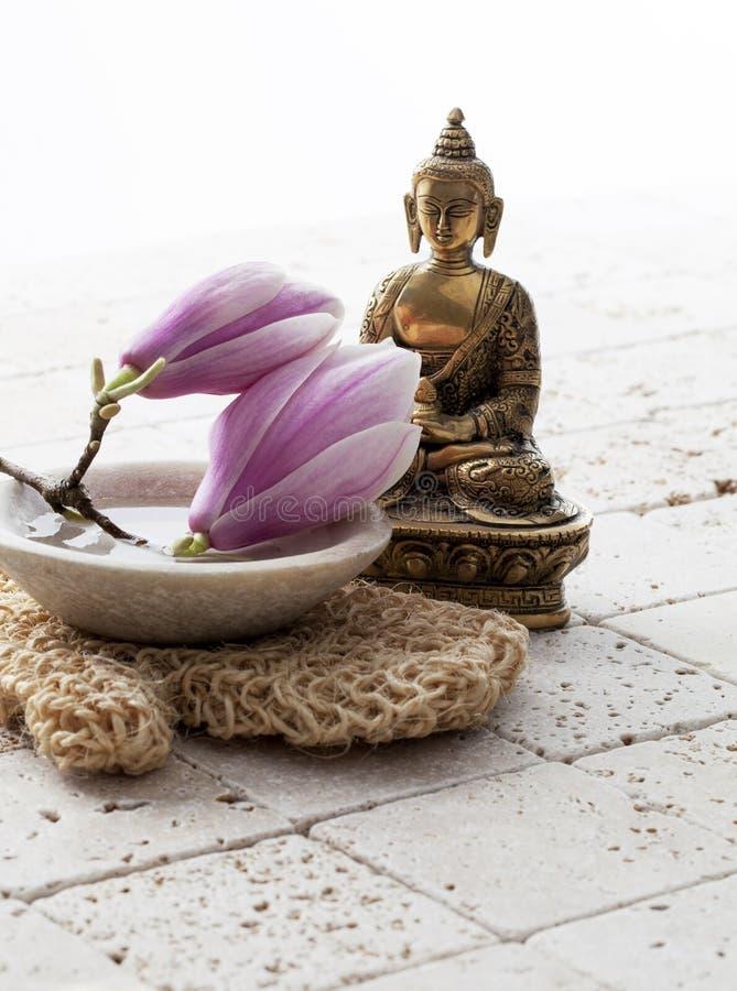Fiori della magnolia accanto a Buddha su fondo minerale fotografia stock