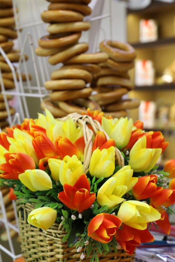 Fiori della primavera nella priorità alta Un mazzo dei tulipani artificiali sta in un canestro di vimini immagine stock