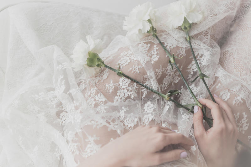 Fiori della tenuta della ragazza su lei rivestimento fotografie stock libere da diritti