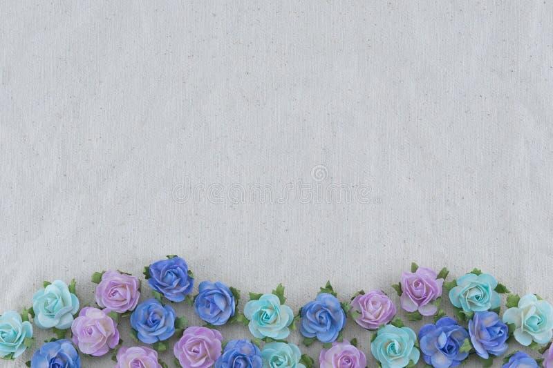 Fiori di carta della rosa blu di tono sul tessuto della mussola immagine stock