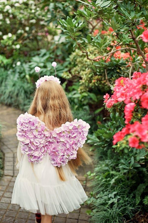 fiori di fiuto della ragazza delle azalee azalee di fioritura nel parco Ragazza con le ali viola della farfalla Tiro di foto fant fotografia stock libera da diritti