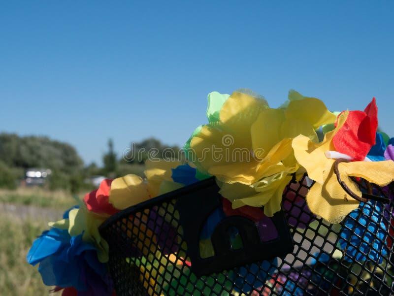 Fiori di plastica artificiali che decorano un canestro della bici fotografia stock libera da diritti
