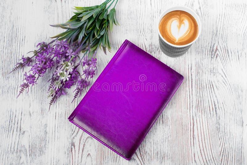 Fiori di porpora di una tazza di caffè del blocco note fotografie stock