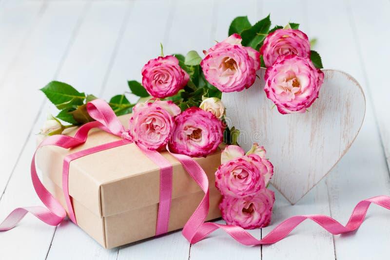 Fiori di Rosa, cuore di legno e contenitore di regalo sulla tavola rustica blu Bella cartolina d'auguri per il giorno di complean immagine stock libera da diritti