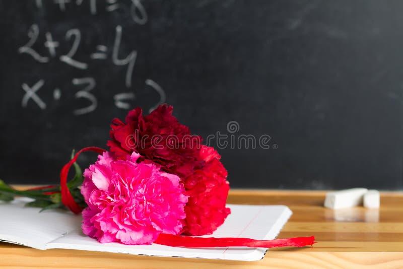 Fiori e lavagna nel concetto del fondo di giorno dell'insegnante dell'aula immagini stock