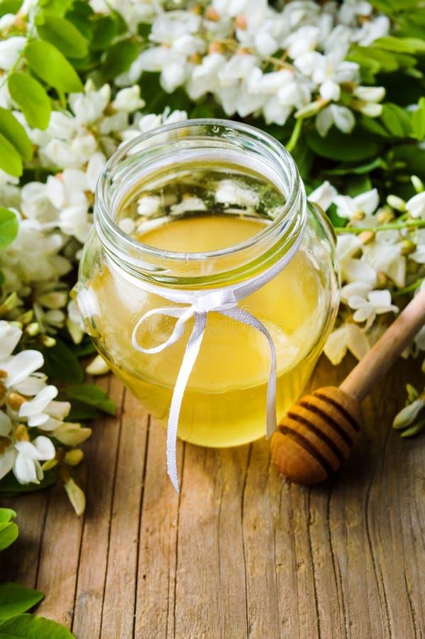 Fiori e miele dell'acacia nel barattolo immagine stock libera da diritti