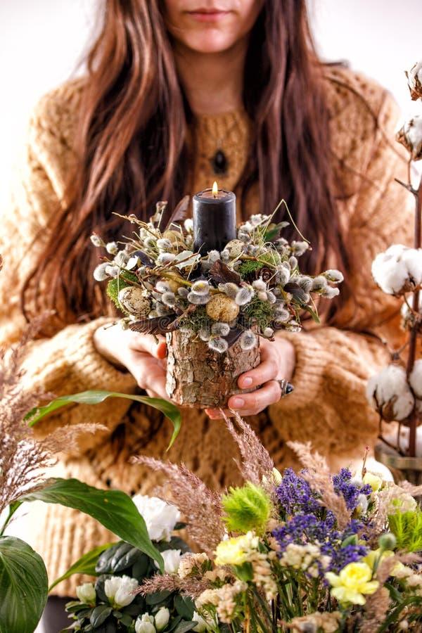 Fiori e rami secchi del salice nelle mani di una ragazza decorazioni, candele, rami asciutti del salice e una mano femminile Il c fotografia stock