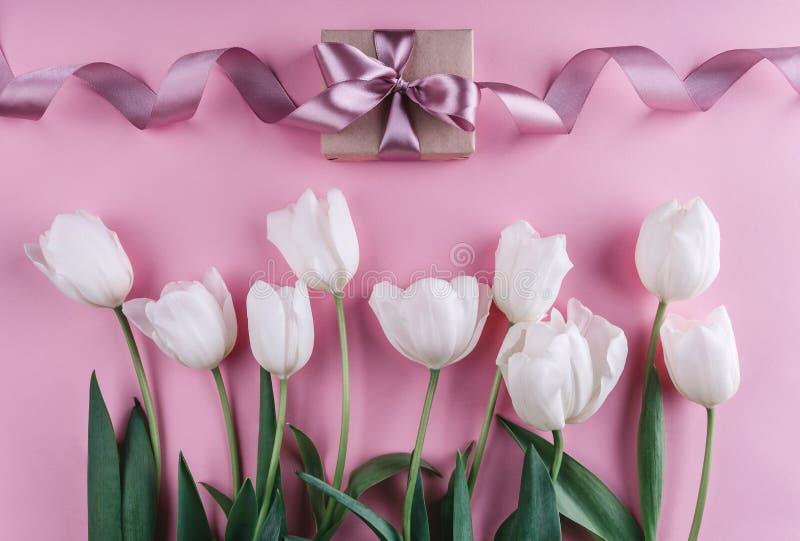 Fiori e regalo bianchi dei tulipani sopra fondo rosa-chiaro Cartolina d'auguri o invito di nozze fotografia stock libera da diritti